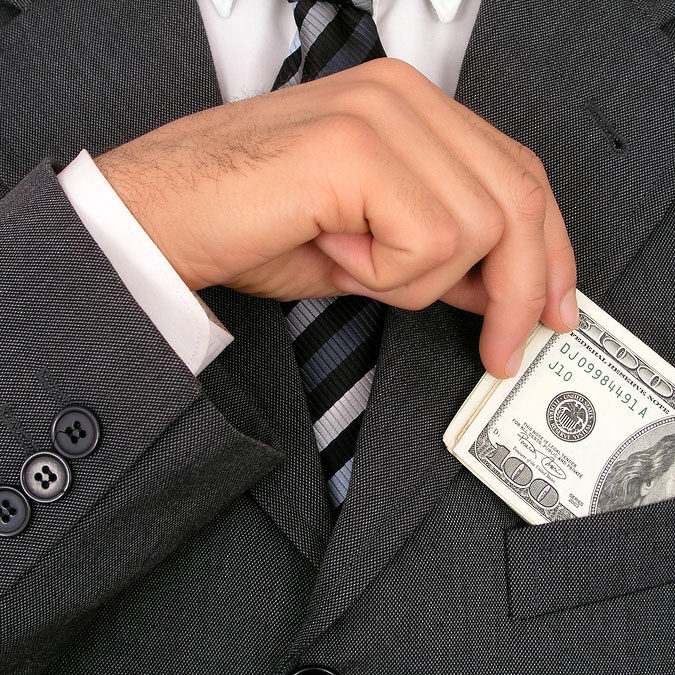 Businessman_Putting Money Into Pocket